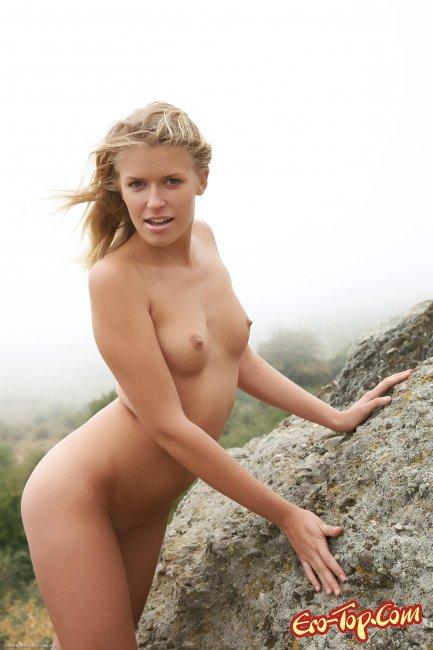 Голая девушка позирует в горах фото