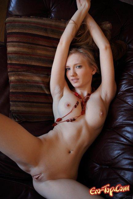Обнаженная девушка лежит на диване фото